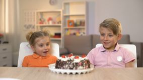 Lächelnde Kinder, die Schokoladenkuchen auf Tabelle, Kindheitsglück, Geschenk betrachten stock footage