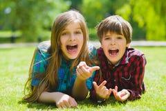 Lächelnde Kinder, die Spaß am Gras haben Kinder, die draußen im Sommer spielen Jugendliche teilen im Freien mit Stockfoto