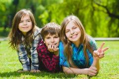 Lächelnde Kinder, die Spaß am Gras haben Kinder, die draußen im Sommer spielen Jugendliche teilen im Freien mit Stockbilder