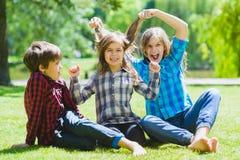Lächelnde Kinder, die Spaß am Gras haben Kinder, die draußen im Sommer spielen Jugendliche teilen im Freien mit Stockfotografie