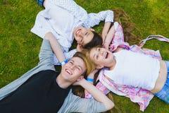 Lächelnde Kinder, die Spaß haben oder an hinter liegen und oben dem Himmel betrachten Kinder, die draußen im Sommer spielen Stockfoto