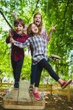 Lächelnde Kinder, die Spaß am Spielplatz haben Kinder, die draußen im Sommer spielen Jugendliche, die draußen auf ein Schwingen f Lizenzfreie Stockfotos