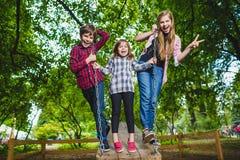 Lächelnde Kinder, die Spaß am Spielplatz haben Kinder, die draußen im Sommer spielen Jugendliche, die draußen auf ein Schwingen f Stockbild
