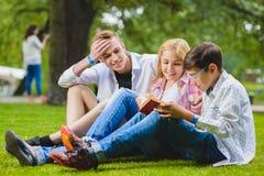 Lächelnde Kinder, die Spaß- und Lesebuch am Gras haben Kinder, die draußen im Sommer spielen Jugendliche teilen im Freien mit Stockfotos