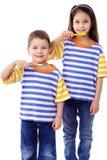 Lächelnde Kinder, die zusammen Zähne putzen Stockbild