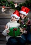 Lächelnde Kinder mit Weihnachtsgeschenk und Baum des neuen Jahres. Herstellung des Geschenkes. Stockfoto