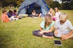 Lächelnde Kinder schauen ihre Tablette mit anderen Kindern hinter ihnen lizenzfreie stockfotos