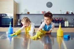Lächelnde Kinder tun die Reinigung in der Küche lizenzfreie stockfotografie