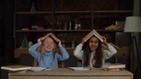 Lächelnde kleine Mädchen mit Büchern über ihren Köpfen stock footage