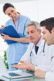 Lächelnde Krankenschwester, die auf Doktoren sprechen über etwas auf Th hört Stockbilder