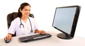 Lächelnde Krankenschwester, die an ihrem Schreibtisch sitzt Stockfotografie