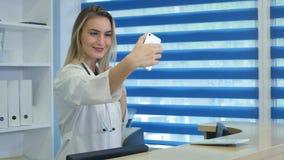 Lächelnde Krankenschwester, die selfies mit ihrem Telefon hinter Aufnahmeschreibtisch nimmt Lizenzfreie Stockfotos