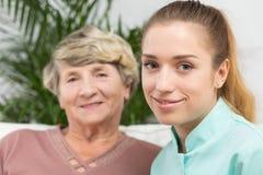Lächelnde Krankenschwester mit einer älteren Dame Stockfotografie