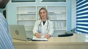 Lächelnde Krankenschwester mit Terminplanungsverabredung des Laptops für männlichen Patienten an der Aufnahme Lizenzfreie Stockfotos
