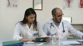 Lächelnde Krankenschwester und ihr männlicher Mitarbeiter, die versucht, Tablette aber sie zu benutzen ` s nicht arbeitend stock video