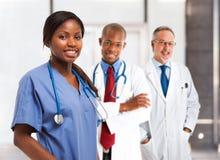 Lächelnde Krankenschwester vor ihrem Ärzteteam lizenzfreie stockfotografie