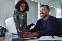 Lächelnde kreative Kollegen, die im Büro zusammenarbeiten lizenzfreie stockbilder