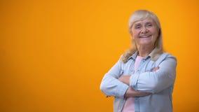 Lächelnde Kreuzungshände der alten Frau auf Kasten, erfolgreiches Geschäft, glückliches Erwachsensein stock video