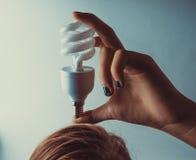 Lächelnde Lampe Mädchen, das Glühlampe auf Kopf hält Stockfotos