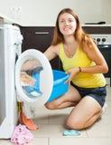 Lächelnde langhaarige Frau, die Waschmaschine verwendet Stockfoto