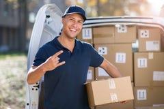 Lächelnde Liefererstellung vor seinem Packwagen, der ein Paket hält lizenzfreies stockfoto