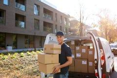 Lächelnde Liefererstellung vor seinem Packwagen, der ein Paket hält stockfoto