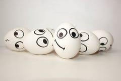 Lächelnde lustige Eier mit einem Gesicht auf einem Weiß Lizenzfreies Stockfoto