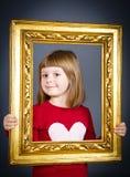 Lächelnde Mädchen, die durch einen WeinleseBilderrahmen schauen Stockfotografie