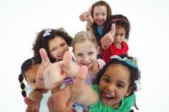 Lächelnde Mädchen, die ganz aufwärts mit den Daumen oben schauen Lizenzfreie Stockfotos