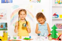 Lächelnde Mädchen malen Bälle des neuen Jahres für Weihnachtsbaum Lizenzfreie Stockbilder