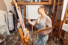 Lächelnde Mädchenfarben auf Segeltuch mit Ölfarben in der Werkstatt Lizenzfreie Stockfotografie