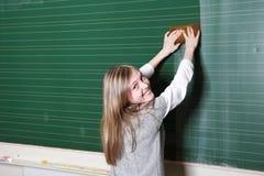 Lächelnde Mädchenreinigungs-Schuletafel Stockbild