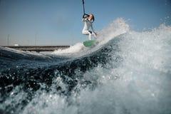 Lächelnde Mädchenstellung auf dem wakeboard, das ein Seil hält lizenzfreie stockbilder