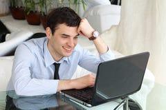 Lächelnde Männer denken und arbeiten am Laptop Lizenzfreie Stockbilder