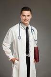 Lächelnde männliche Krankenschwester, die mit rotem Laptop aufwirft Lizenzfreies Stockfoto