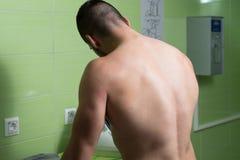 Lächelnde Mann-bügelnde Kleidung an der Waschküche Stockfoto