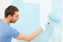 Lächelnde Mannmalereiwand zu Hause stockbild