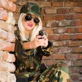 Lächelnde Militärfrau mit Gewehr Stockbild