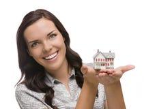 Lächelnde Mischrasse-Frau, die kleines Haus lokalisiert auf Weiß hält Stockbilder