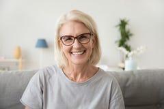 Lächelnde Mitte alterte die reife graue behaarte Frau, die Kamera betrachtet lizenzfreies stockbild