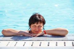 Lächelnde Mittelalterfrau, die im Swimmingpool sich entspannt Stockbild