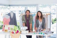 Lächelnde Modedesigner, die auf Schreibtisch sich lehnen Stockbilder
