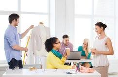 Lächelnde Modedesigner, die im Büro arbeiten Stockfotos