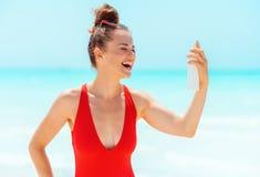 Lächelnde moderne Frau auf dem Strand, der Sonnenschutz anwendet stockbild