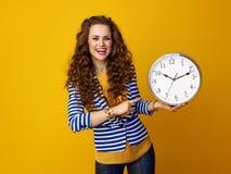 Lächelnde moderne Frau auf gelbem Hintergrund zeigend auf Uhr Stockfotos