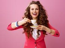 Lächelnde moderne Frau lokalisiert auf Rosa mit Tasse Kaffee Lizenzfreie Stockbilder