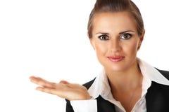Lächelnde moderne Geschäftsfrau, die etwas darstellt Stockbild