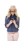 Lächelnde modische blonde Versenden von SMS-Nachrichten Lizenzfreies Stockbild