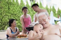 Lächelnde multi-Generations-Afamilie, die im Urlaub durch das Pool barbequing ist Stockfoto