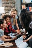Lächelnde multiethnische Frauen, die digitale Tablette beim Büro zu Hause bearbeiten betrachten Stockfoto
